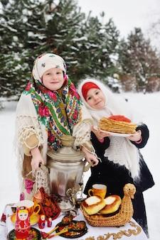 Duas meninas em casacos de pele e xales em estilo russo