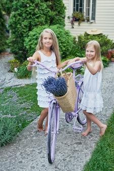 Duas meninas em chapéus com uma cesta de lavanda em um jardim de verão