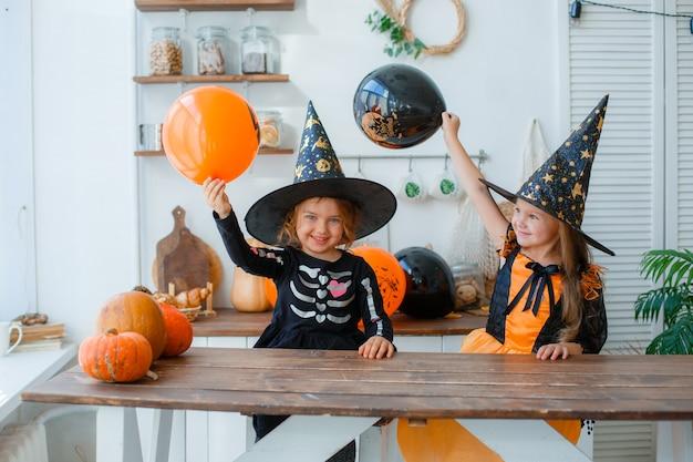 Duas meninas em fantasias de bruxa para o sorriso de halloween