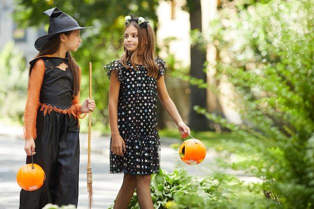 Duas meninas em fantasias de halloween segurando sacolas em forma de abóboras indo para guloseimas ao ar livre
