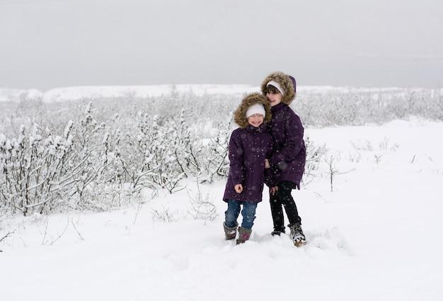 Duas meninas em jaquetas idênticas conversam em um campo coberto de neve durante uma nevasca