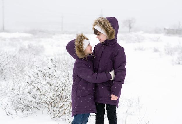 Duas meninas em jaquetas idênticas conversam em um campo coberto de neve durante uma nevasca Foto Premium