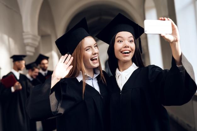 Duas meninas em mantos pretos estão fazendo selfie.