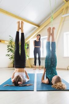 Duas meninas em roupas esportivas, praticando ioga, realizam o exercício da vela, pose de sarvangasana, sob a orientação de seu treinador