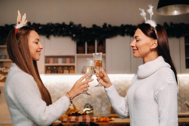 Duas meninas em um ambiente familiar aconchegante com champanhe nas mãos no natal. meninas sorridentes bebem champanhe em uma noite festiva.