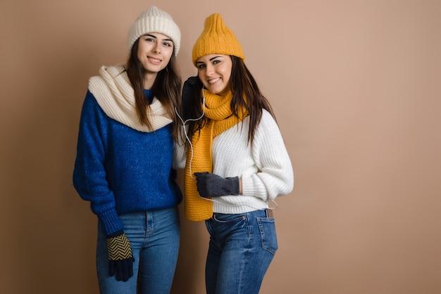 Duas meninas em um cachecol e chapéu ouvir música. sobre um fundo marrom