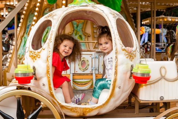 Duas meninas em um carrossel. meninas da princesa cinderela em uma carruagem.