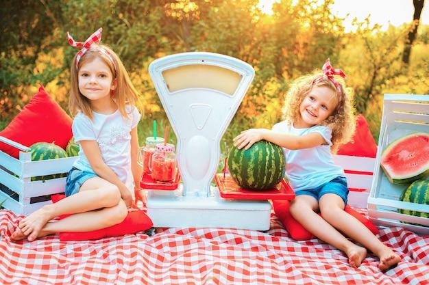 Duas meninas em uma camiseta branca e uma bandana vermelha sentam-se em um tapete na natureza e seguram uma melancia e uma jarra com suco, que fica em uma balança à moda antiga. conceito de vendas