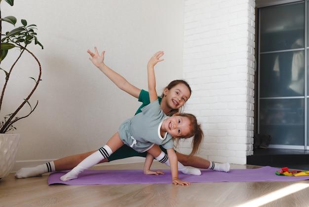 Duas meninas em uniformes esportivos fazem exercícios em casa