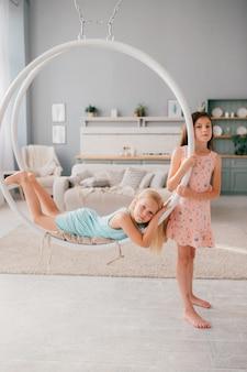 Duas meninas em vestidos bonitos, montando o balanço e posando