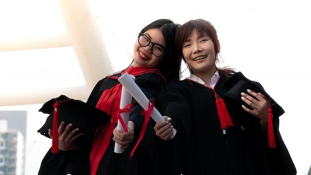 Duas meninas em vestidos pretos e certificado do diploma da preensão que sorriem com graduado feliz.