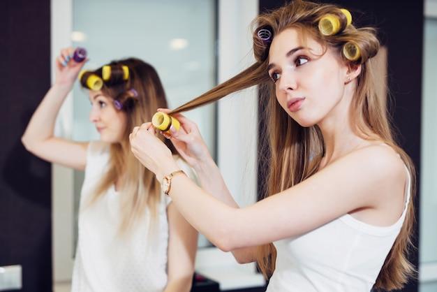 Duas meninas enchendo seus cabelos com rolos em uma sala