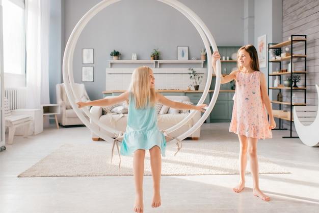 Duas meninas engraçadas em vestidos bonitos, montando o balanço e posando