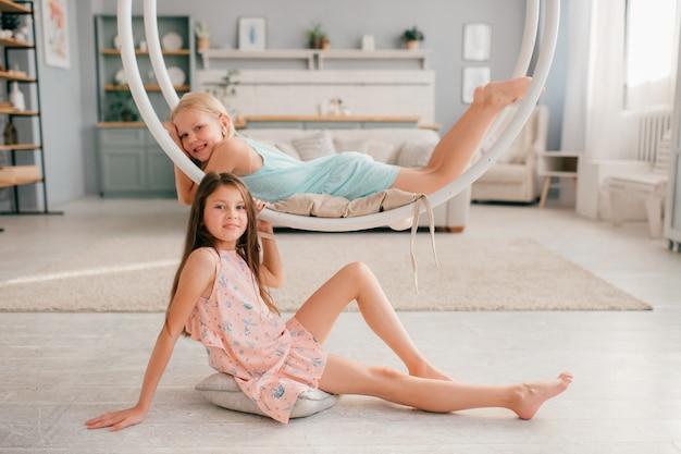 Duas meninas engraçadas em vestidos bonitos, posando em casa