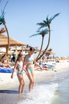 Duas meninas estão em uma praia de areia em maiôs azuis contra o fundo de palmeiras artificiais e olham para baixo