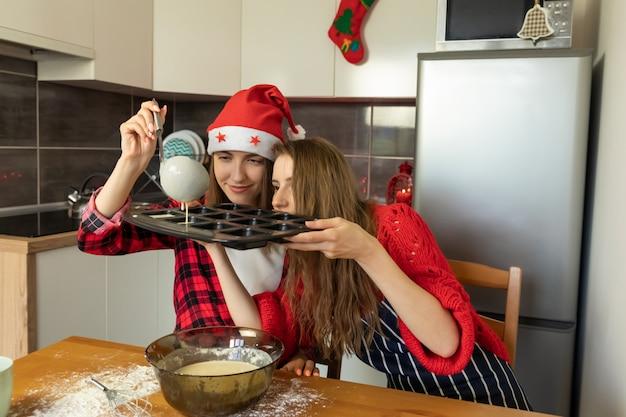 Duas meninas estão preparando biscoitos de natal em casa na cozinha. t