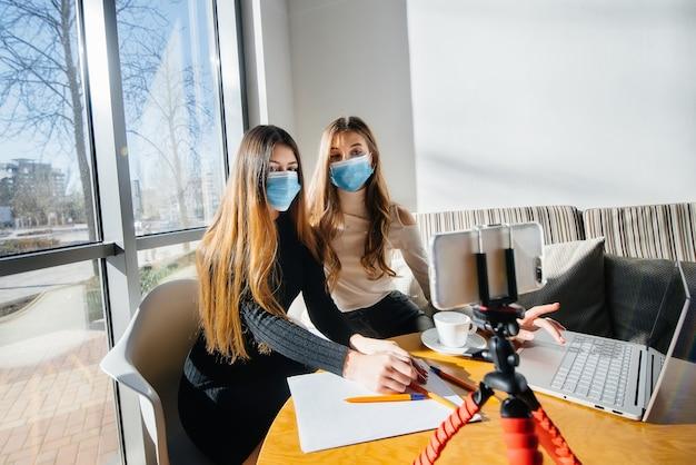 Duas meninas estão sentadas em um café mascaradas e conduzem um videoblog. comunicação com a câmera.