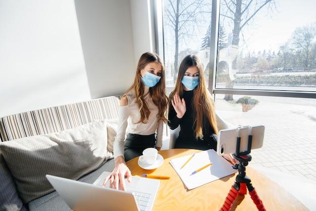 Duas meninas estão sentadas em um café mascaradas e conduzem um videoblog