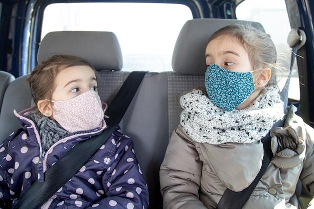 Duas meninas estão sentadas em um carro no banco de trás, usando máscaras durante a pandemia.