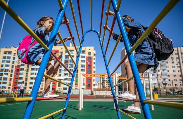 Duas meninas, estudantes do ensino fundamental, brincam no parquinho depois da escola.