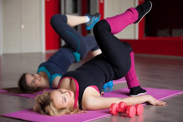 Duas meninas fazem exercícios aeróbicos em tapetes no centro de fitness