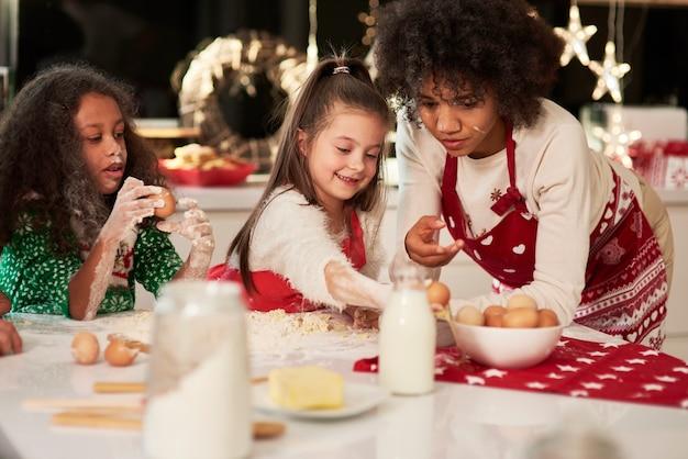 Duas meninas fazendo biscoitos com a mãe no natal