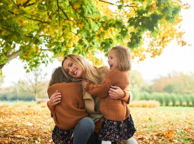 Duas meninas felizes abraçando a mamãe