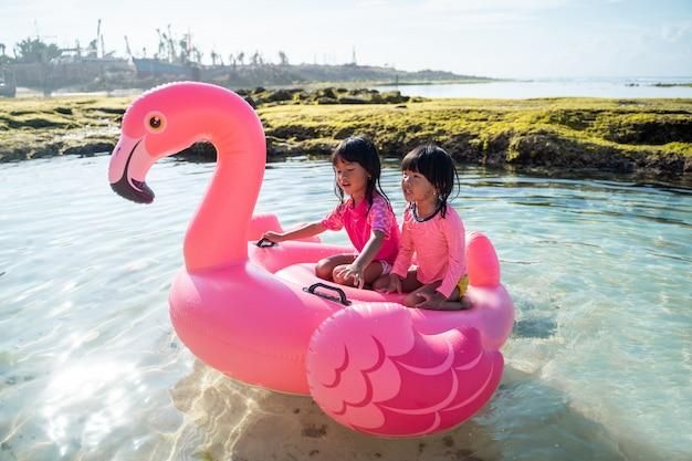 Duas meninas felizes andando em uma bóia de flamingo