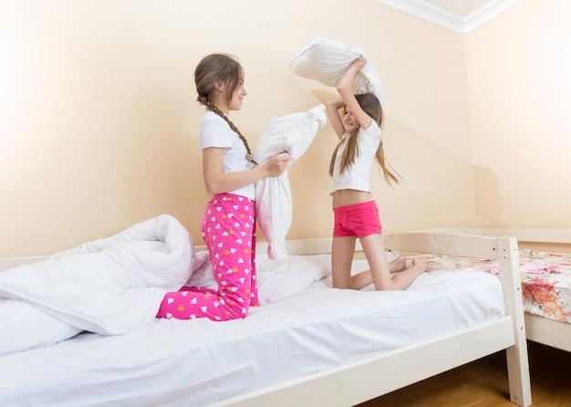 Duas meninas felizes brigando com almofadas no quarto