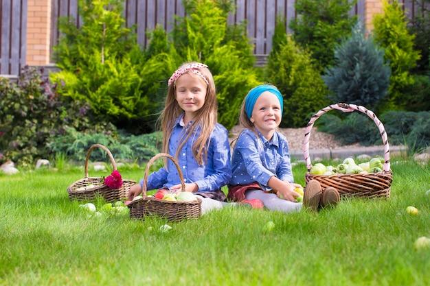 Duas meninas felizes com grande colheita de outono de tomates