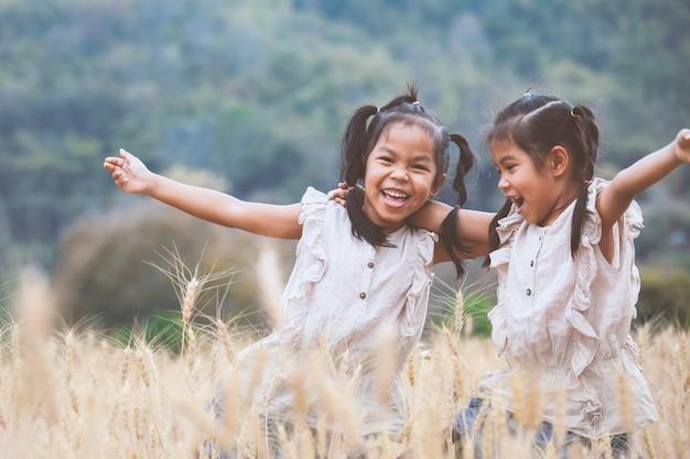 Duas meninas felizes da criança asiática se divertindo para jogar juntos no campo de cevada