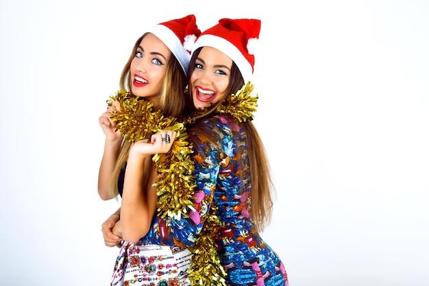 Duas meninas felizes e malucas, melhores amigas, prontas para celebrar a festa de ano novo, segurando enfeites e gritando