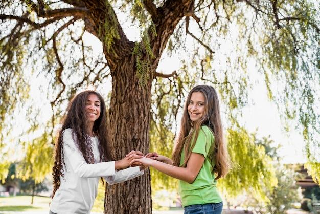 Duas meninas felizes em pé na frente da árvore, segurando as mãos um do outro