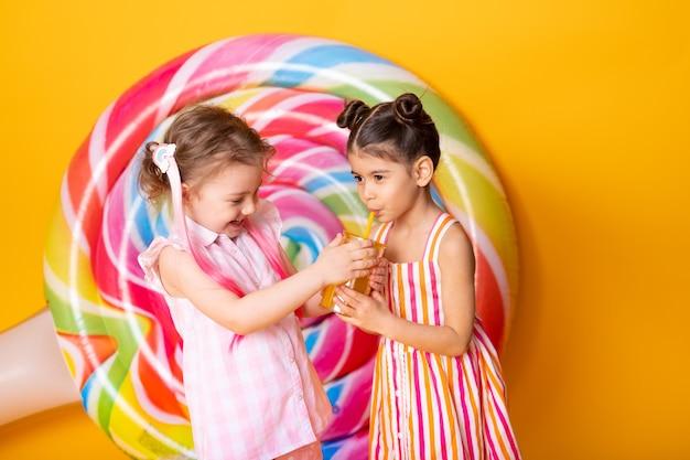 Duas meninas felizes em um vestido colorido, bebendo suco de laranja, se divertindo com o pirulito.