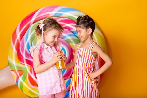 Duas meninas felizes em um vestido colorido, bebendo suco de laranja, se divertindo em um fundo amarelo com ...