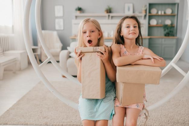 Duas meninas felizes em vestidos bonitos, sentado no balanço com caixas de presente nas mãos no quarto de crianças