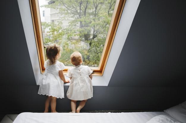 Duas meninas felizes estão olhando alguma coisa na janela