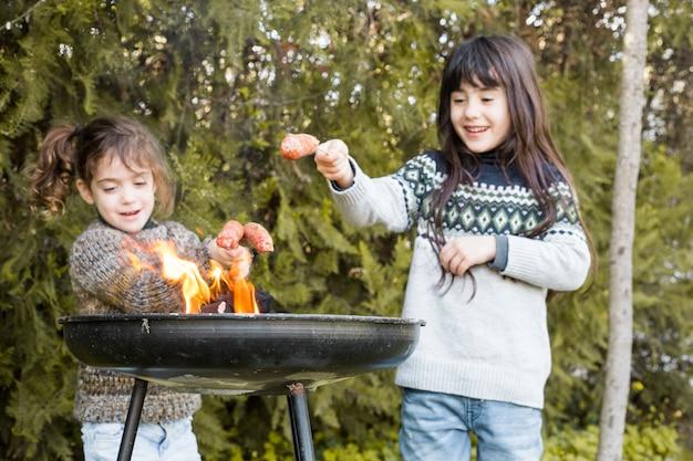 Duas meninas felizes grelhar salsichas em fogo na churrasqueira portátil