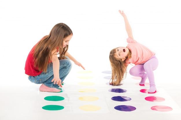 Duas meninas felizes jogam jogo twister