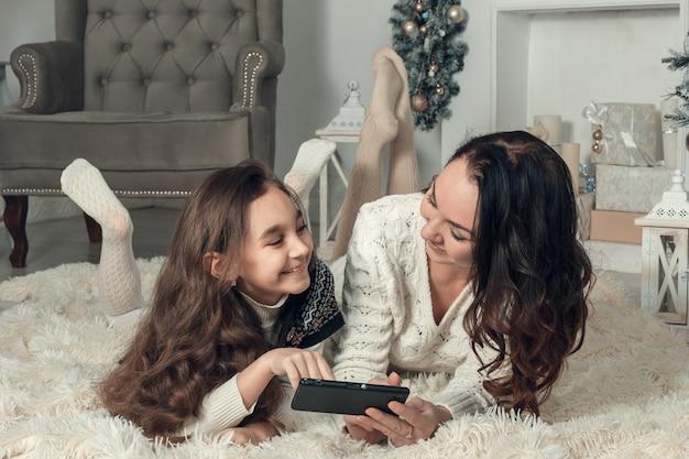 Duas meninas felizes, mãe e filha deitar no chão na sala de natal decorada