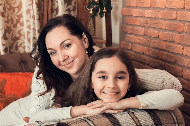 Duas meninas felizes, mãe e filha localização em um sofá na sala de natal decorada.