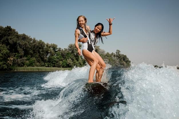 Duas meninas felizes, montando um wakeboard no lago