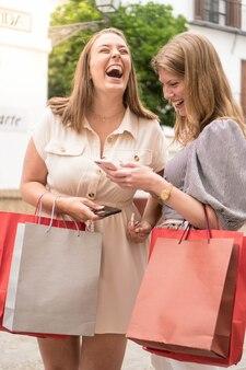 Duas meninas felizes rindo e fofocando com o telefone depois das compras lindas amigas na rua