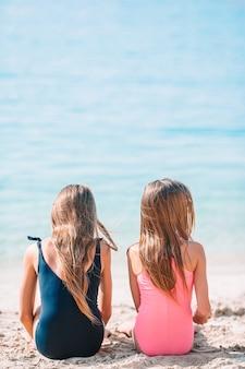 Duas meninas felizes se divertem muito na praia tropical brincando juntas