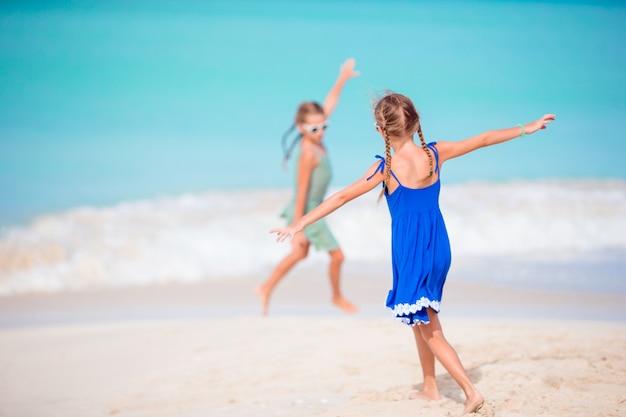 Duas meninas felizes se divertem muito na praia tropical jogando juntos