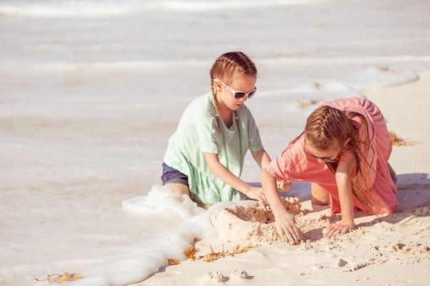 Duas meninas felizes se divertem muito na praia tropical tocando juntos