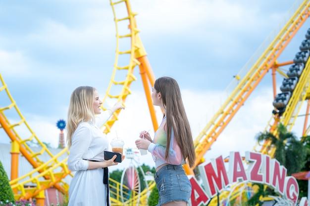 Duas meninas felizes se divertindo em divertimentos enquanto passa o tempo no parque temático.