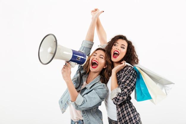 Duas meninas felizes, se divertindo juntos e olhando para longe enquanto gritando no megafone sobre parede branca