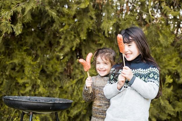 Duas meninas felizes segurando salsichas
