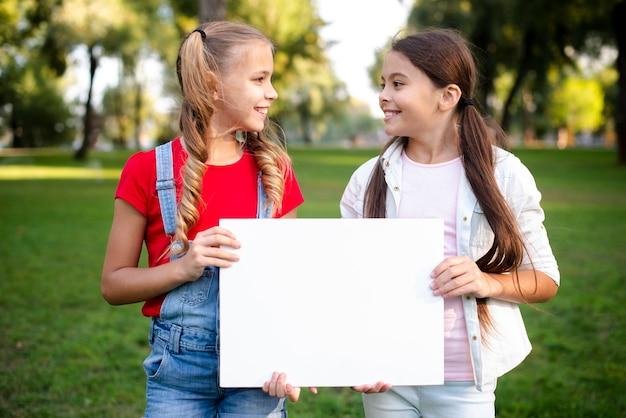 Duas meninas felizes, segurando um papel nas mãos